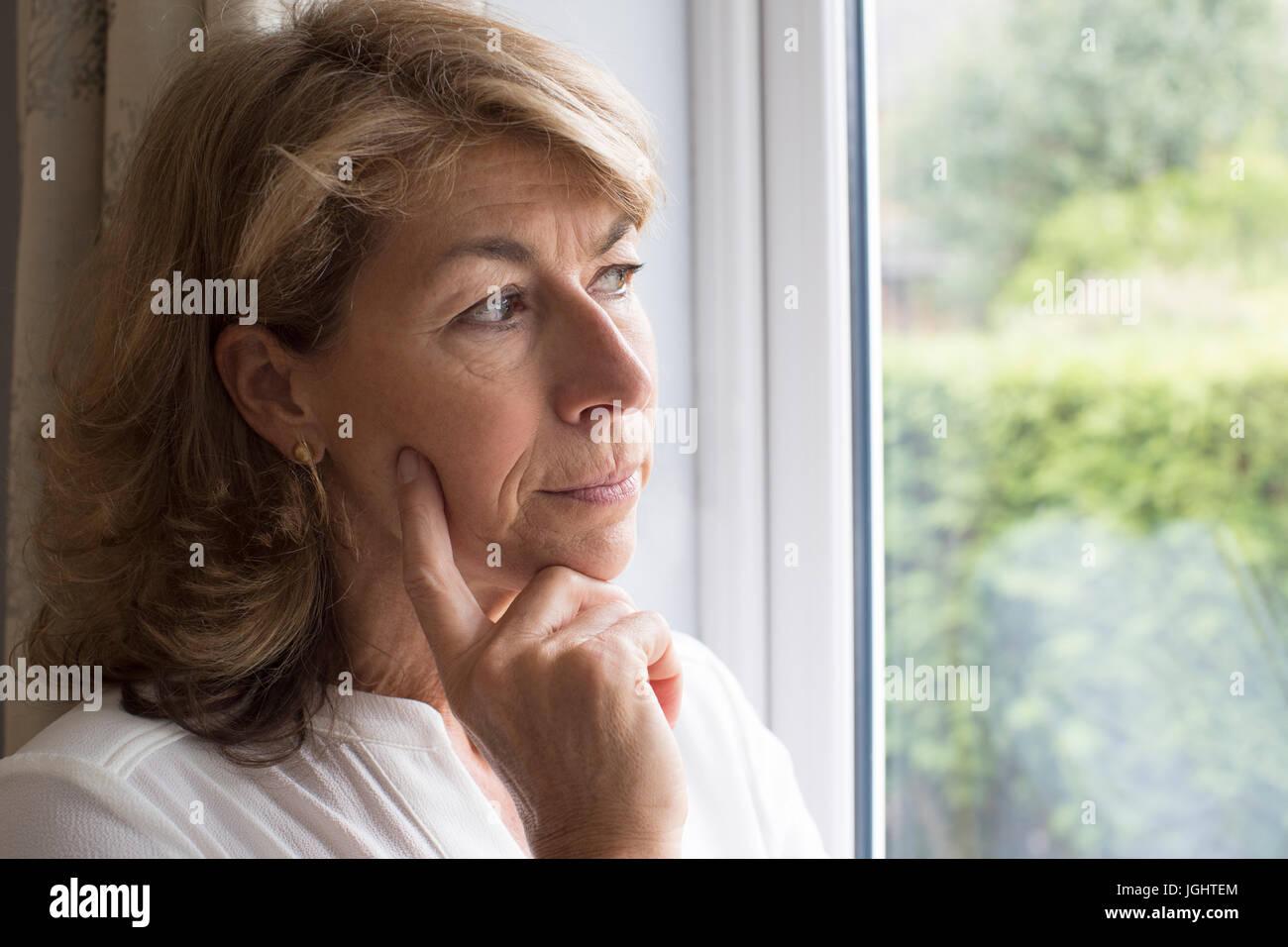 Traurige Frau leidet Agoraphobie Blick aus Fenster Stockbild