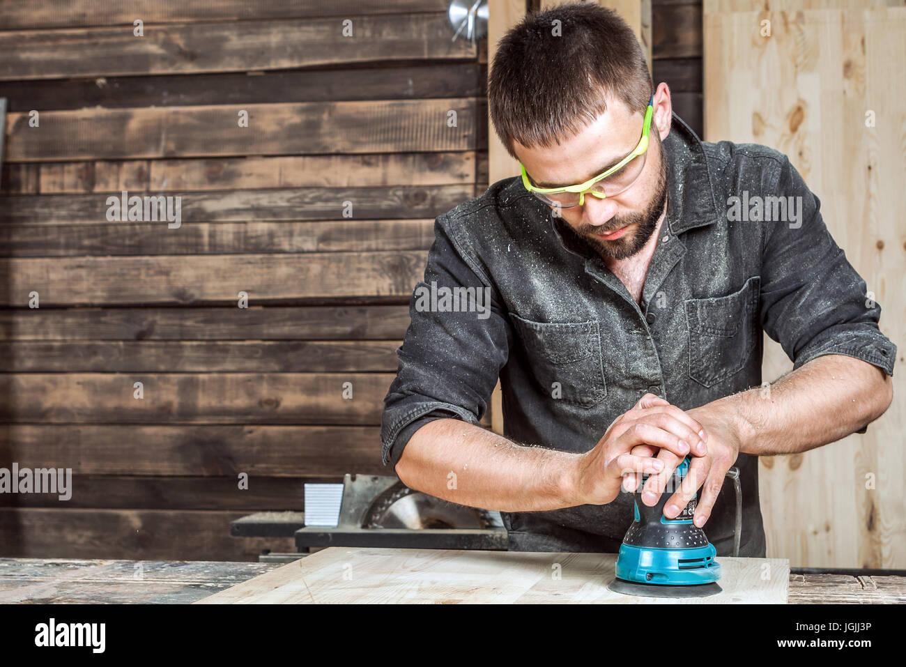 Junge männliche Bauarbeiter Tischler Griffe ein Holzbrett in der ...