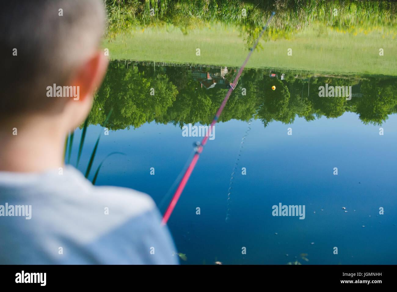Ein Kind angeln an einem Teich in einer ländlichen Gegend. Stockbild