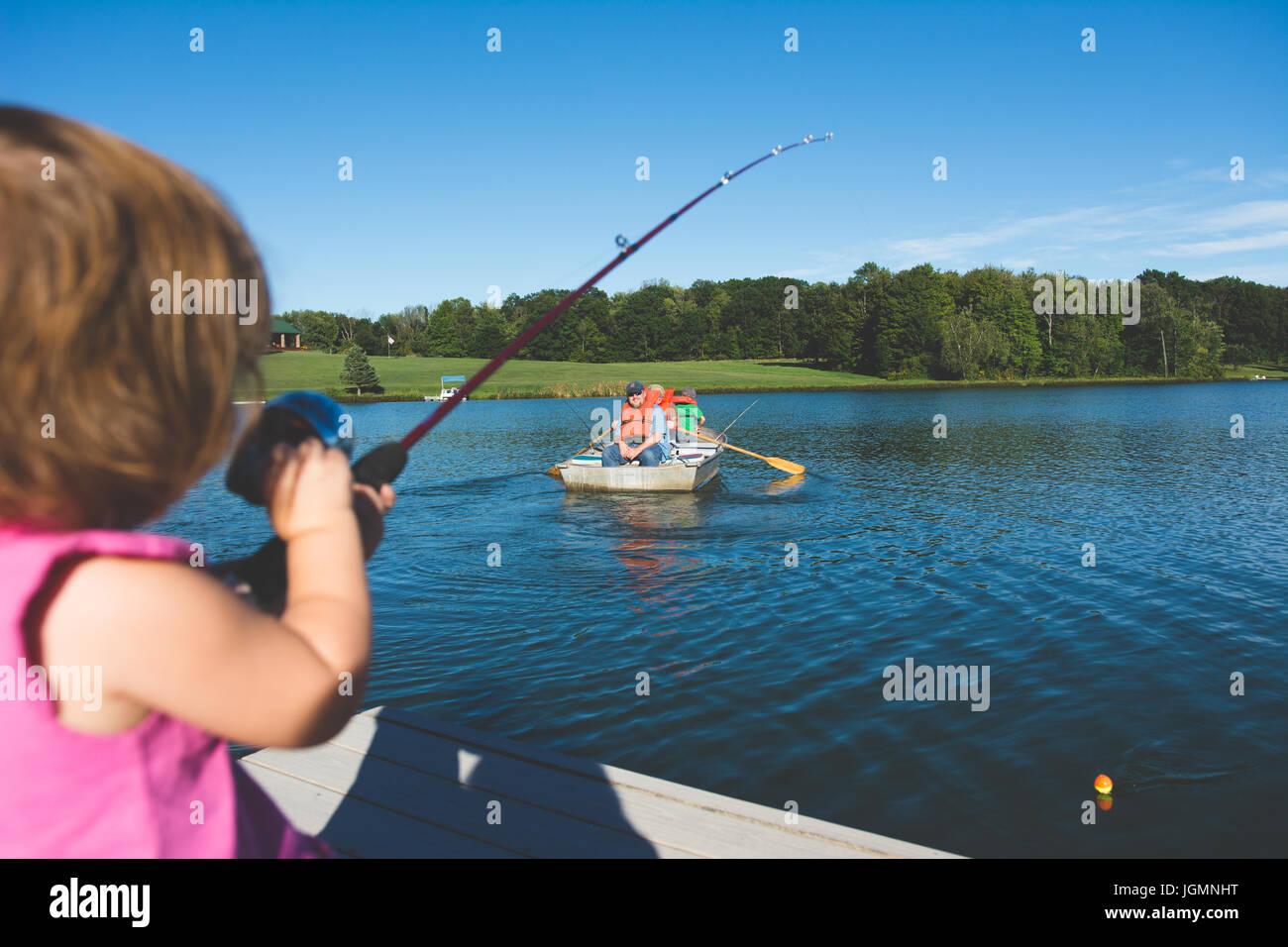 Ein Kind, Angeln an einem Dock an einem Teich in einer ländlichen Gegend. Stockbild