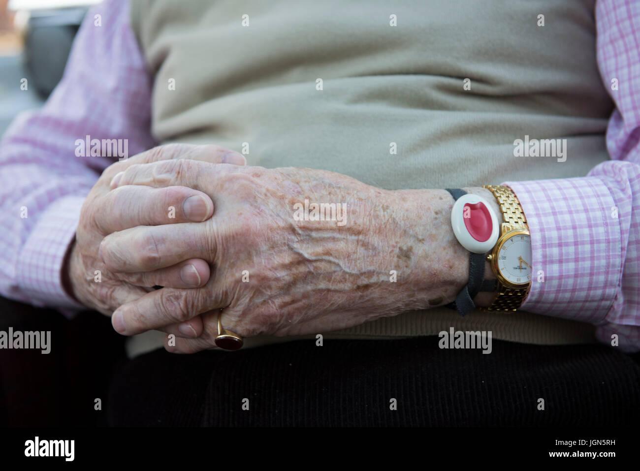 Ein gefährdete Rentner trägt ein Panik-Alarm-Armband. Stockbild