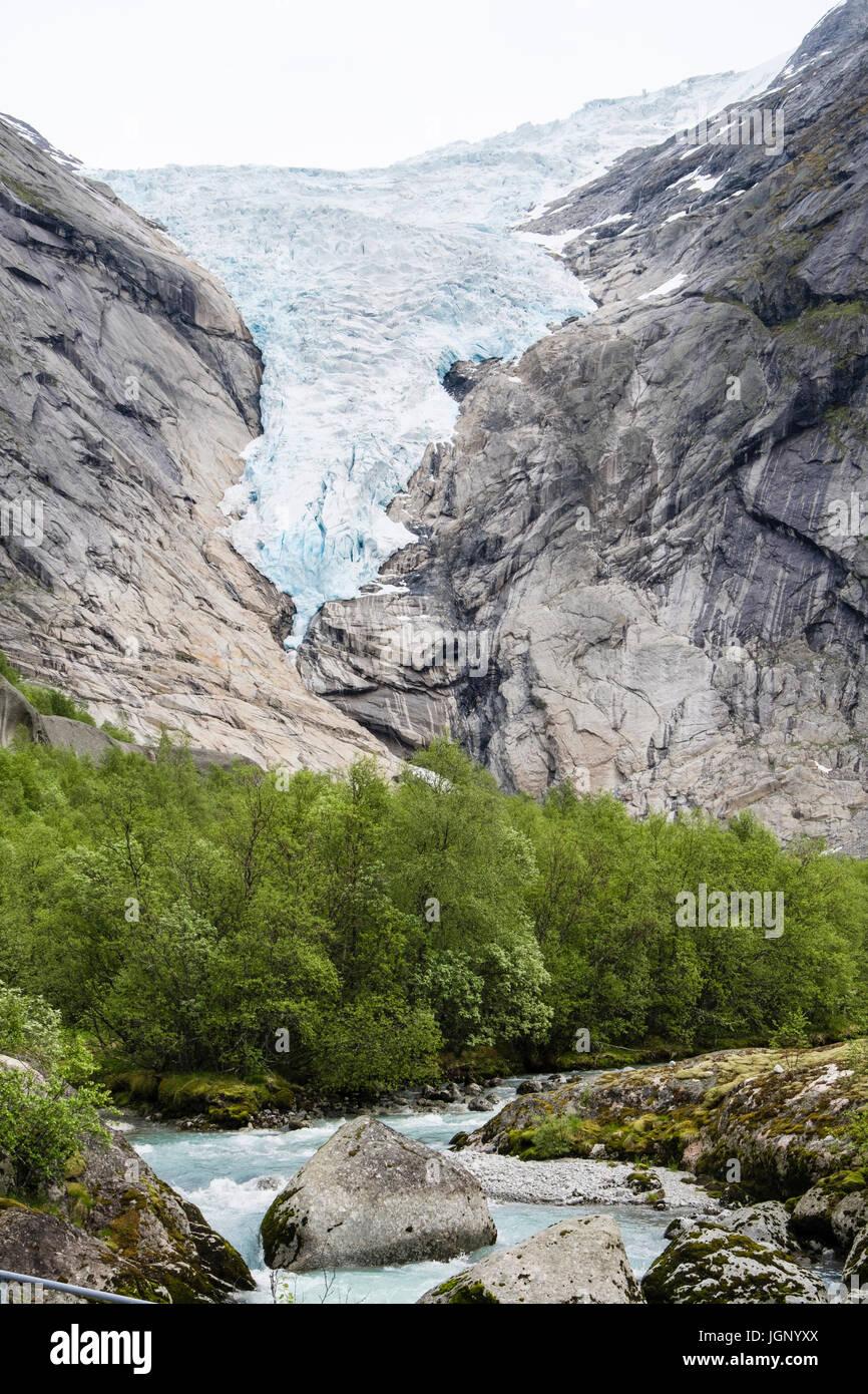 Blick entlang Fluss zum Briksdalsbreen oder Briksdal Gletscher Arm des Jostedalsbreen Gletscher in Briksdalen im Nationalpark Jostedalsbreen im Sommer. Norwegen Stockfoto