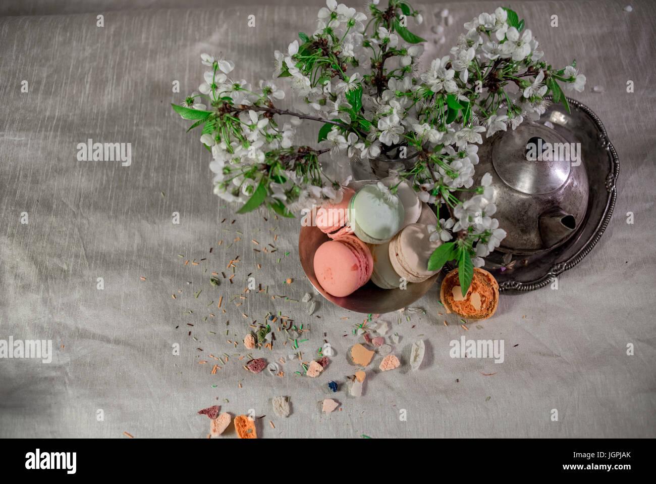 Multicolor Makronen auf einem Tisch mit östlichen Vase und Kirsche Niederlassung in Blüte Stockbild
