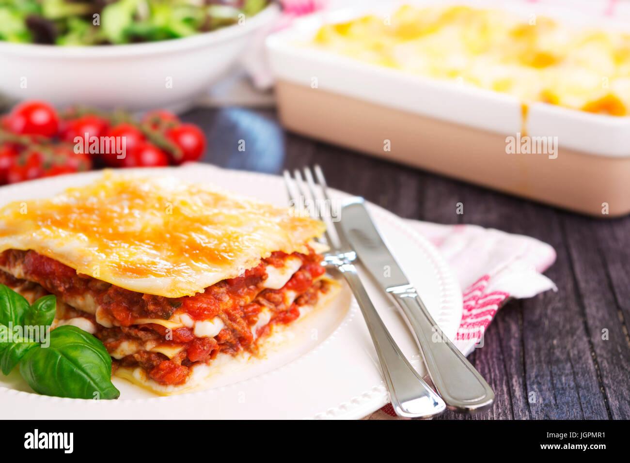 Eine Portion hausgemachte Lasagne auf einer Platte auf einem hell erleuchteten Tisch. Stockbild