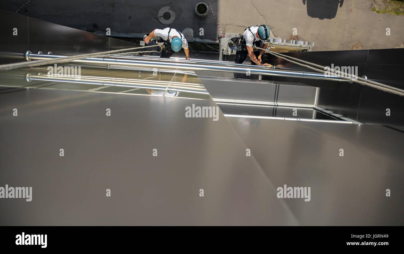 Ein Team von Fenster-Scheiben arbeiten auf einem hohen Bürogebäude Fassade. Stockbild