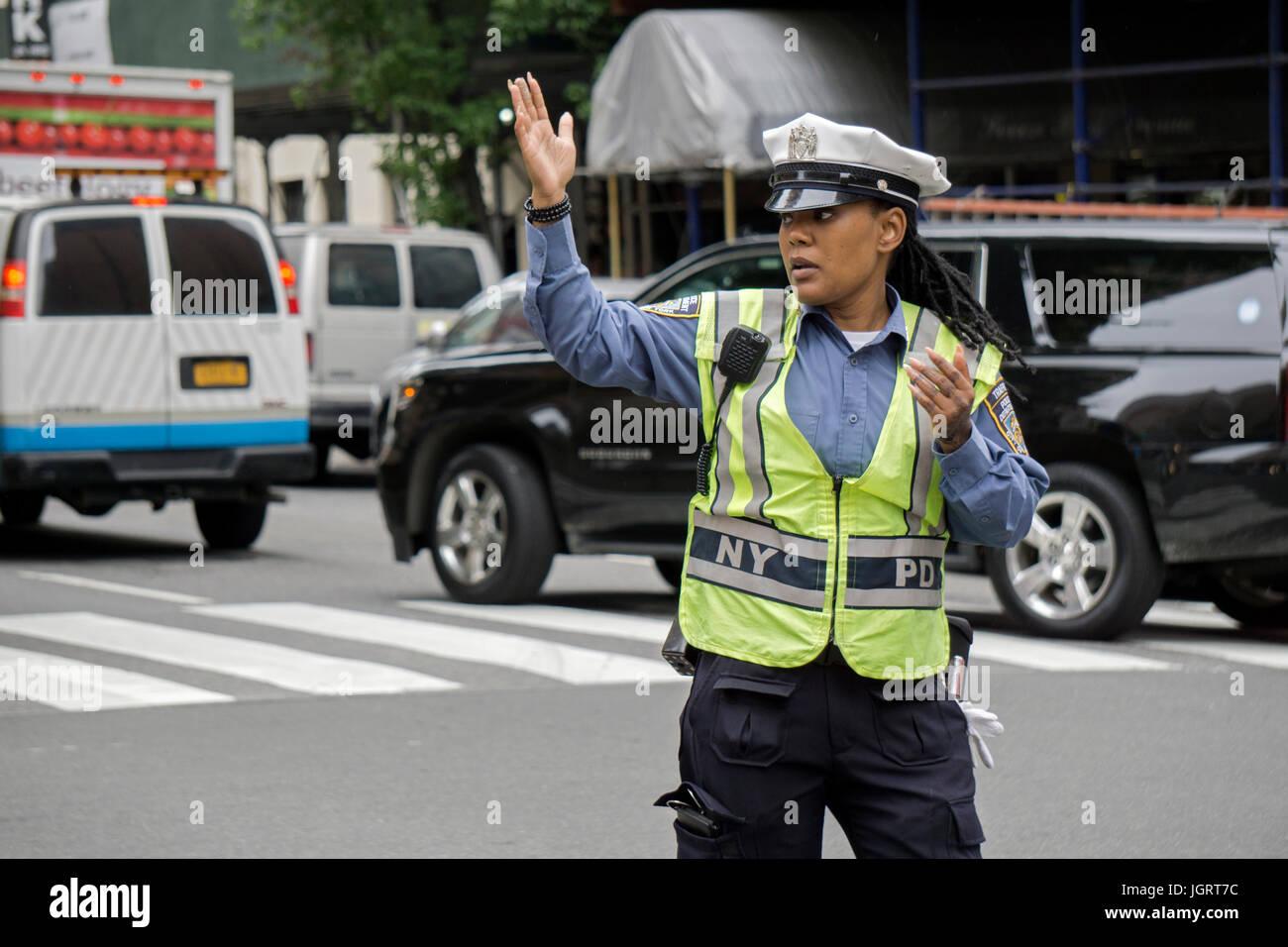 Eine attraktive Polizistin mit langen Fingernägeln, die Regelung des Verkehrs auf der 34th Street in Manhattan, Stockbild