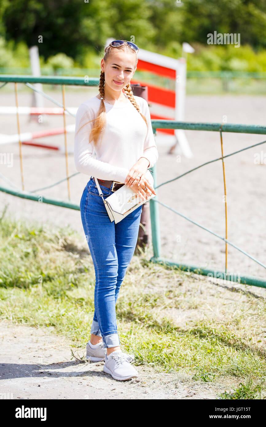 baea3862151d Stilvolle blonde Mädchen mit Zöpfen tragen weiße Sweatshot und blaue jeans
