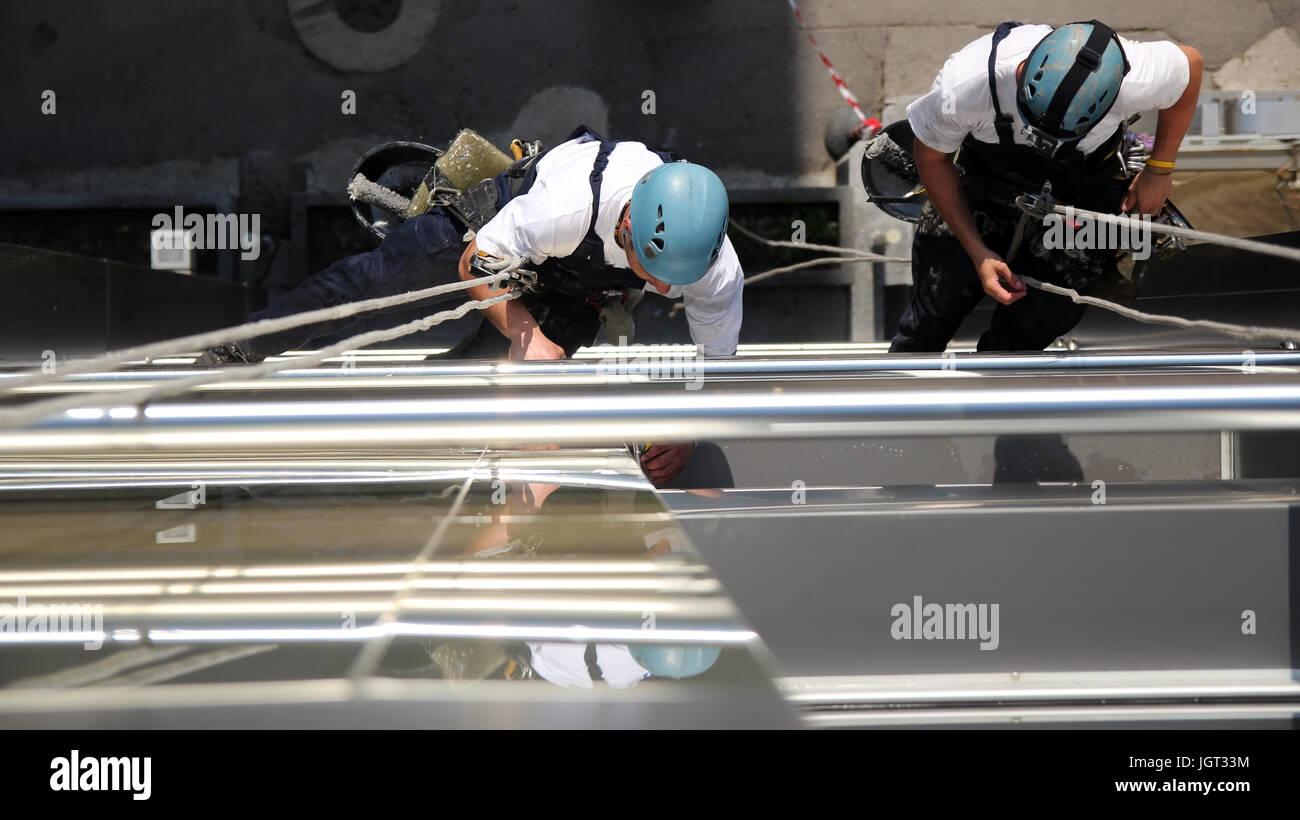 Arbeiter an Kletterseilen und arbeiten zusammen hängen. Stockbild