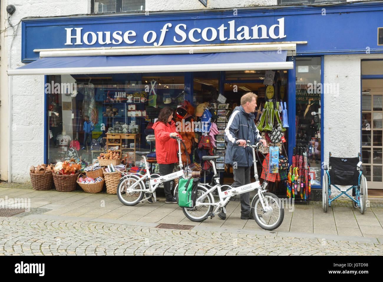 Touristen, die mit elektrischen Falträder außerhalb Souvenirladen in Fort William, Schottland, Großbritannien Stockbild