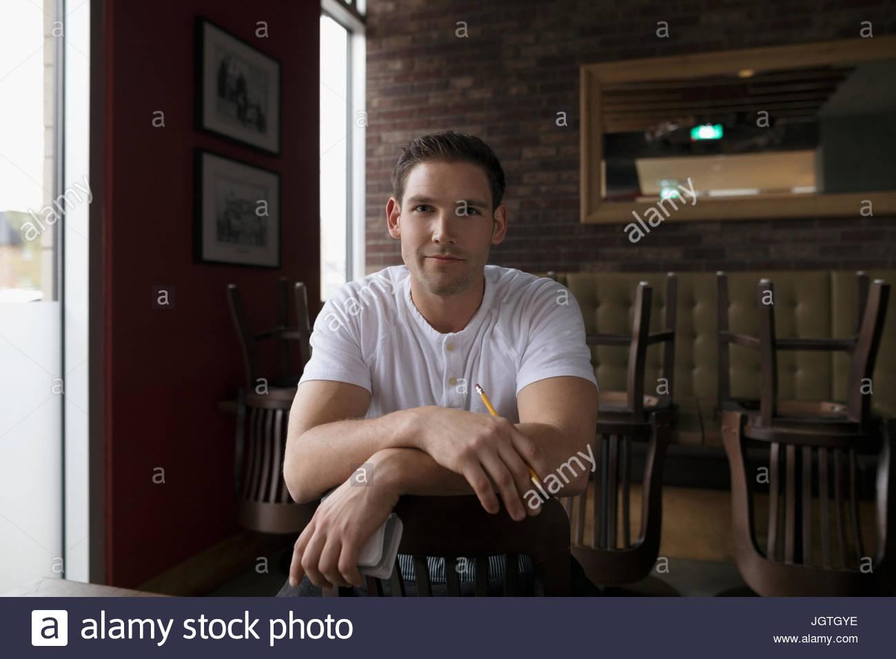 Porträt zuversichtlich Kellner gebietsübergreifenden Stuhl im diner Stockbild