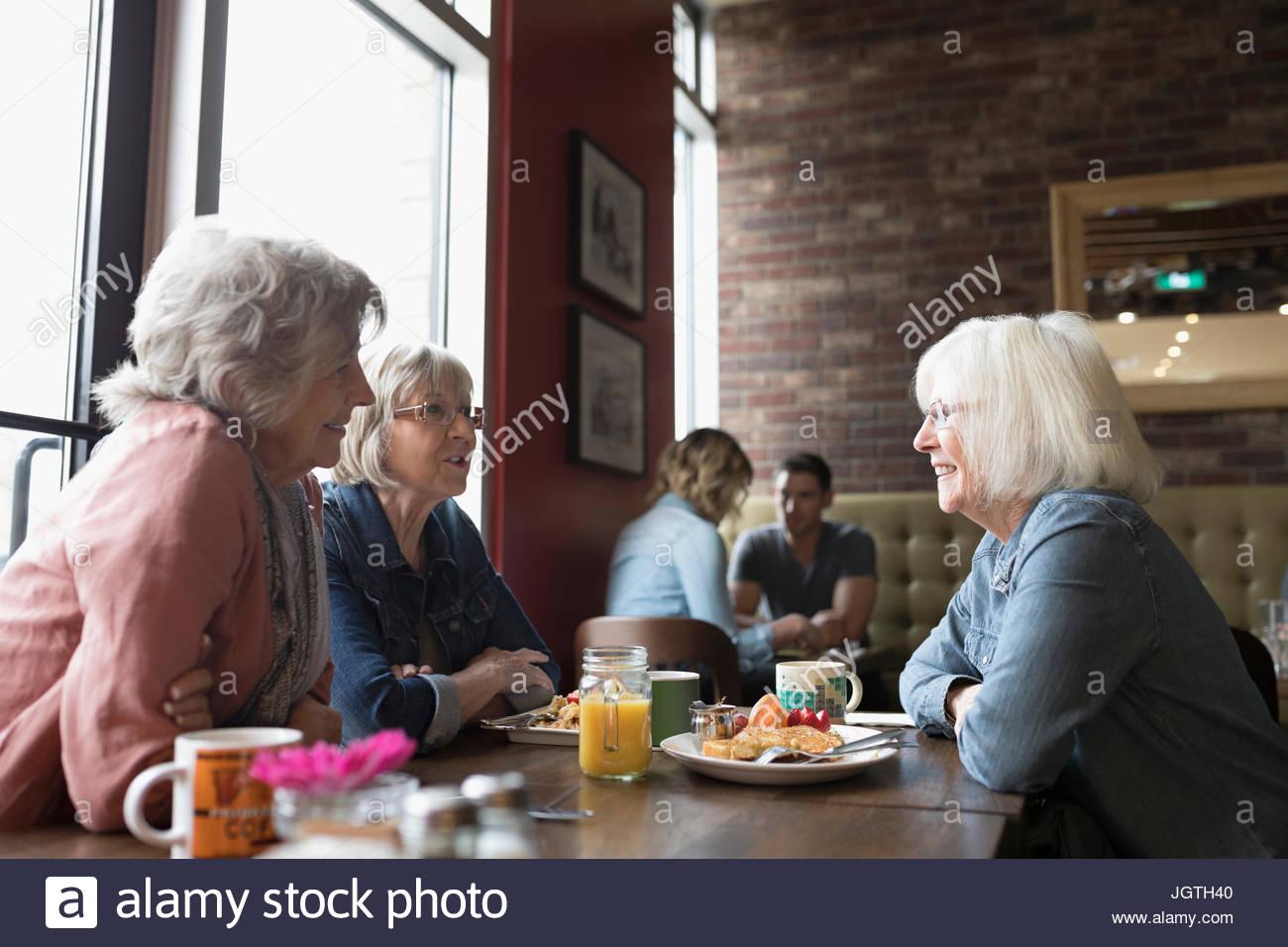 Alte Frauen reden, Essen Brunch an Diner Tisch Stockbild