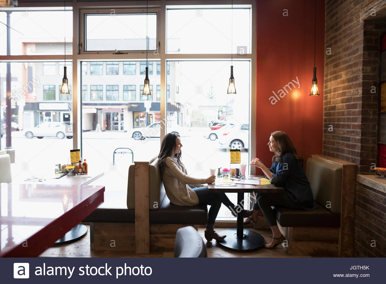 Mutter und Tochter im Teenageralter sprechen, Essen am Imbiss-Stand Stockbild