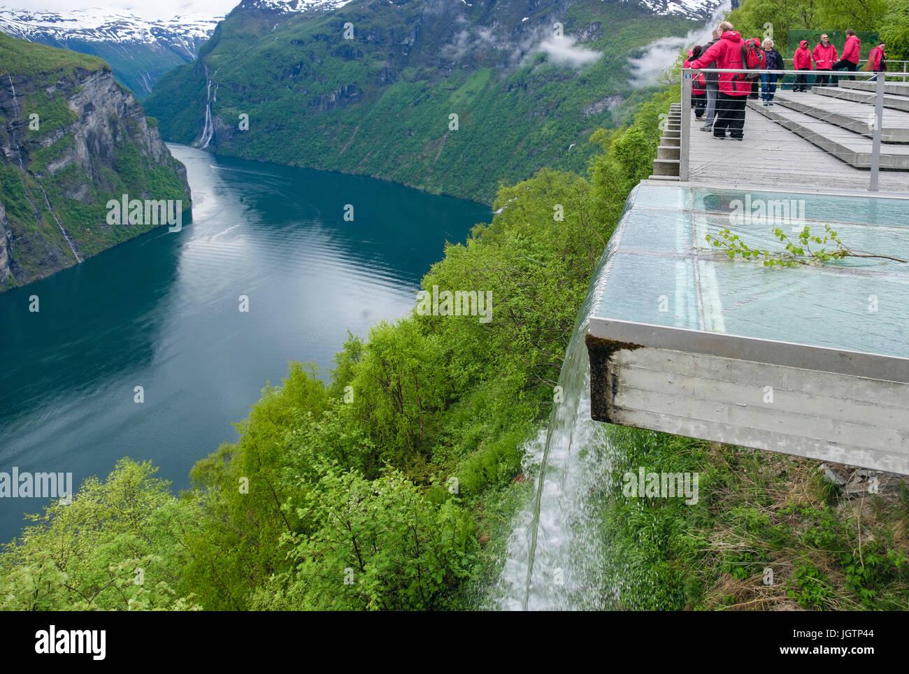Künstlicher Wasserfall mit Touristen betrachten von hohen Adler Straße Sicht Plattform mit Blick auf Geirangerfjord Stockbild