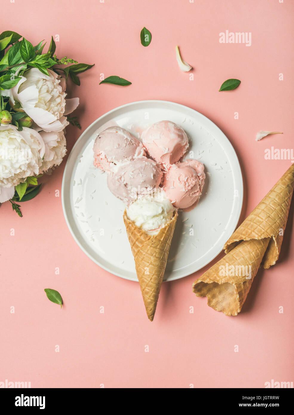 Flatlay Pastell rosa Erdbeer-Kokos-Eis schöpft, süße Zapfen auf weißem Teller und weißen Stockbild
