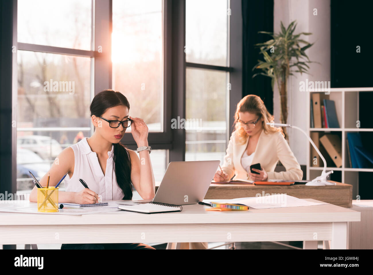junge multiethnischen Geschäftsfrauen in festlich gekleidet im modernen Büro arbeiten Stockbild