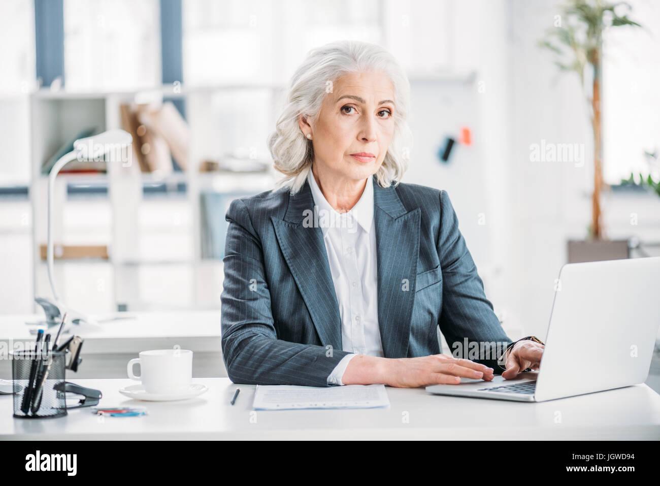 Porträt von zuversichtlich Geschäftsfrau Tippen auf Laptop am Arbeitsplatz im modernen office Stockbild