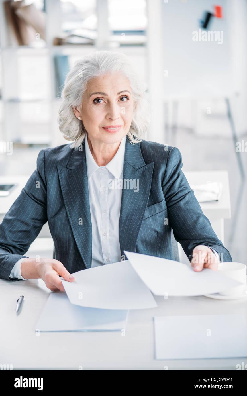Porträt von zuversichtlich senior Geschäftsfrau Papierkram am Arbeitsplatz zu tun Stockbild