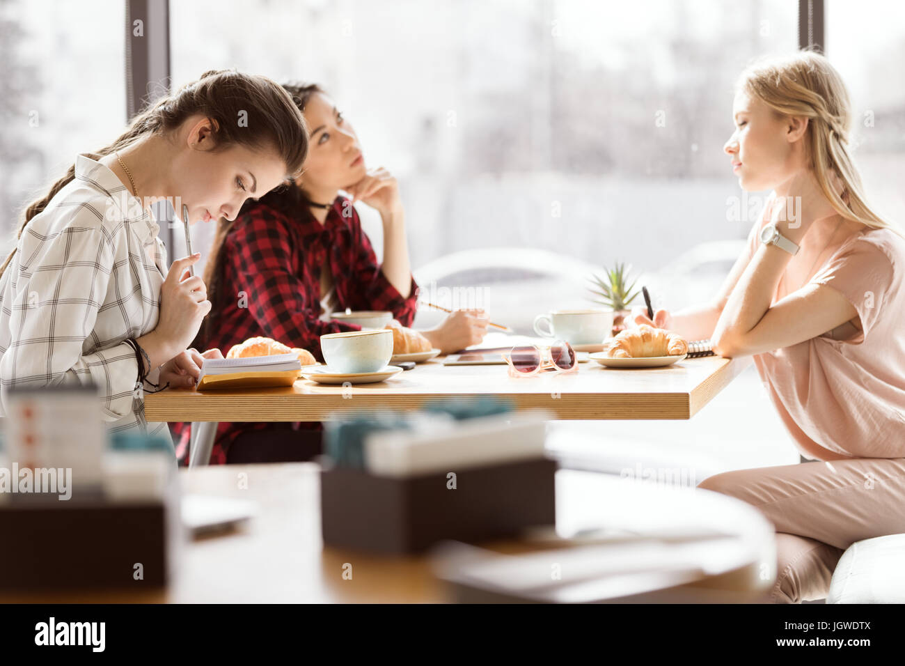 Seitenansicht der Gruppe von Freunden zusammen studieren im café Stockbild