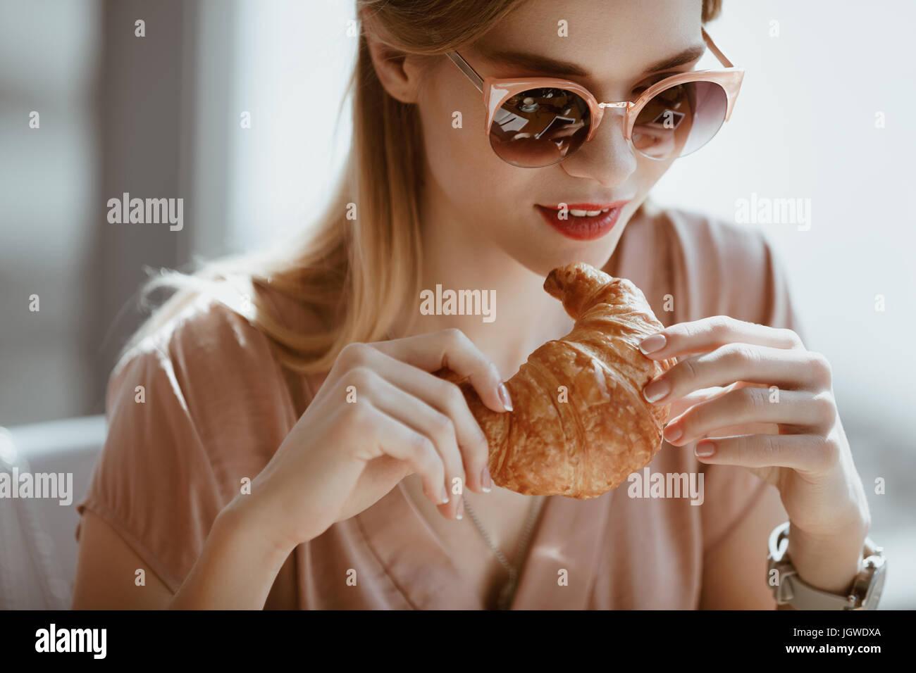 attraktives kaukasische Mädchen in Sonnenbrille mit Croissant im Café mit Mittagessen-Konzept Stockbild