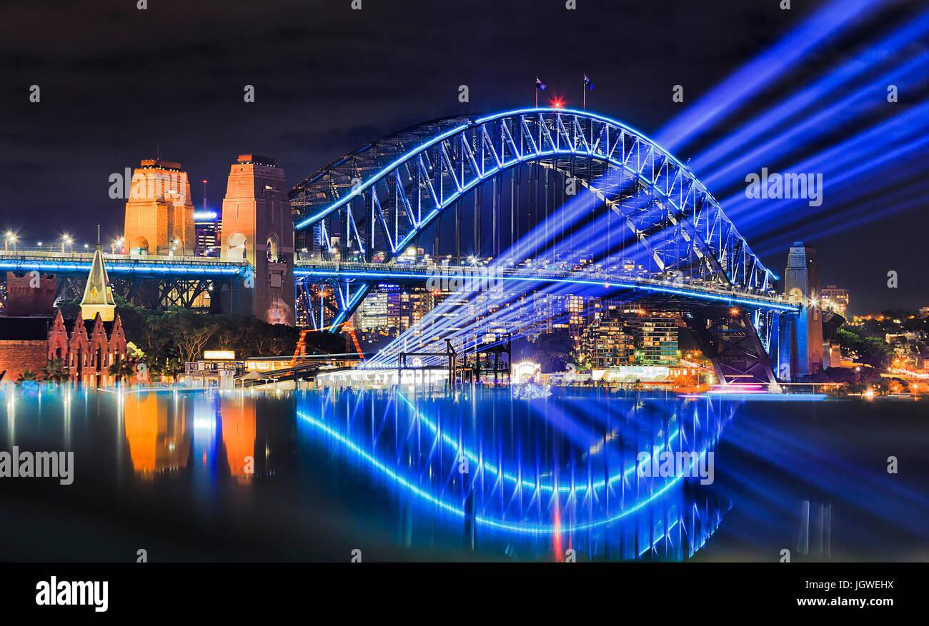 Sydney Hafen-Brücke bei vivid Sydney Lichterfest beleuchtet. Helle blaue Lichtstrahlen Projekt aus Übersee Stockbild