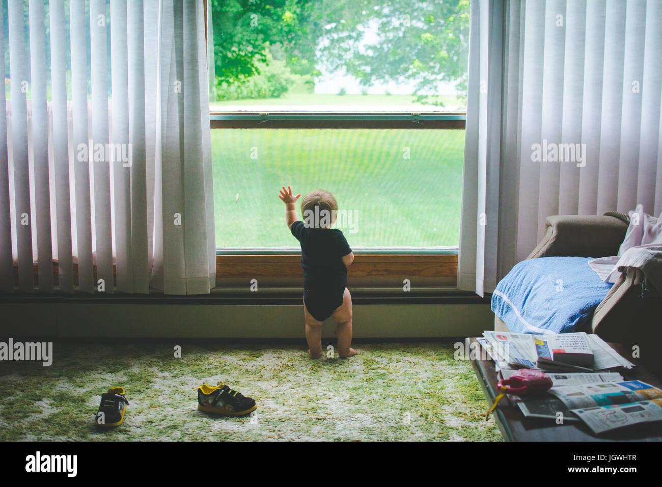 Ein Kind steht mit ihrer Hand in einem Fenster Stockbild