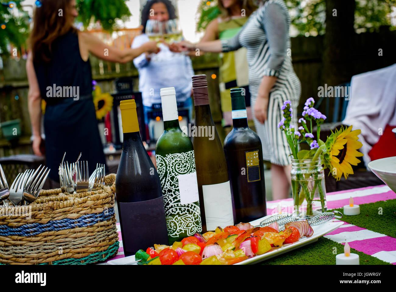 Gruppe von Frauen bei der Gartenparty, Weingläser halten, so dass Toast, Wein-Flaschen auf den Tisch im Vordergrund Stockfoto