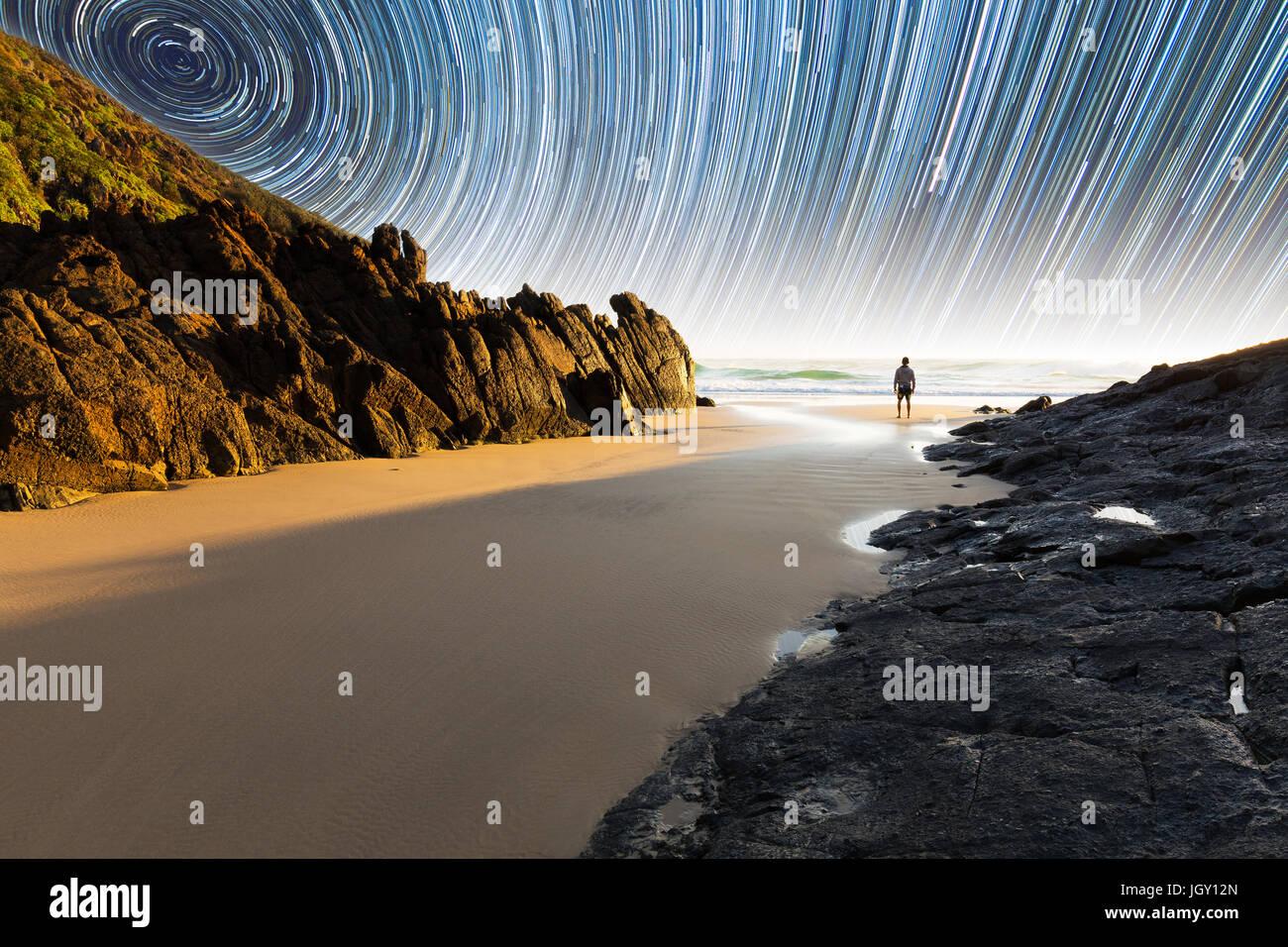 Ein Mann steht auf einem schönen, abgelegenen Strand in Australien unter eine faszinierende Sternspur Stockbild