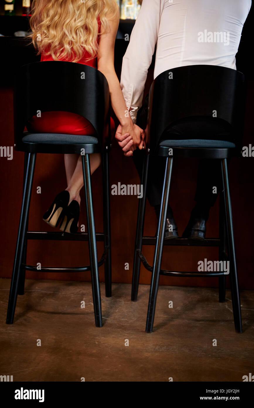 Rückansicht des Paares, die Hand in Hand beim Sitzen am Bar Stockbild