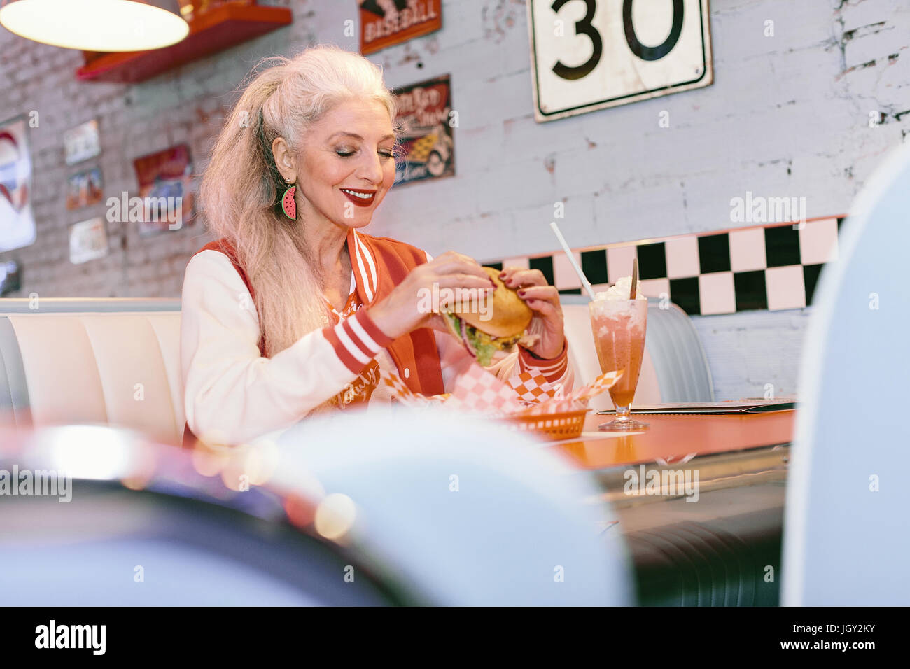 Reife Frau in Baseballjacke Burger im 50er Jahre Diner Essen Stockbild