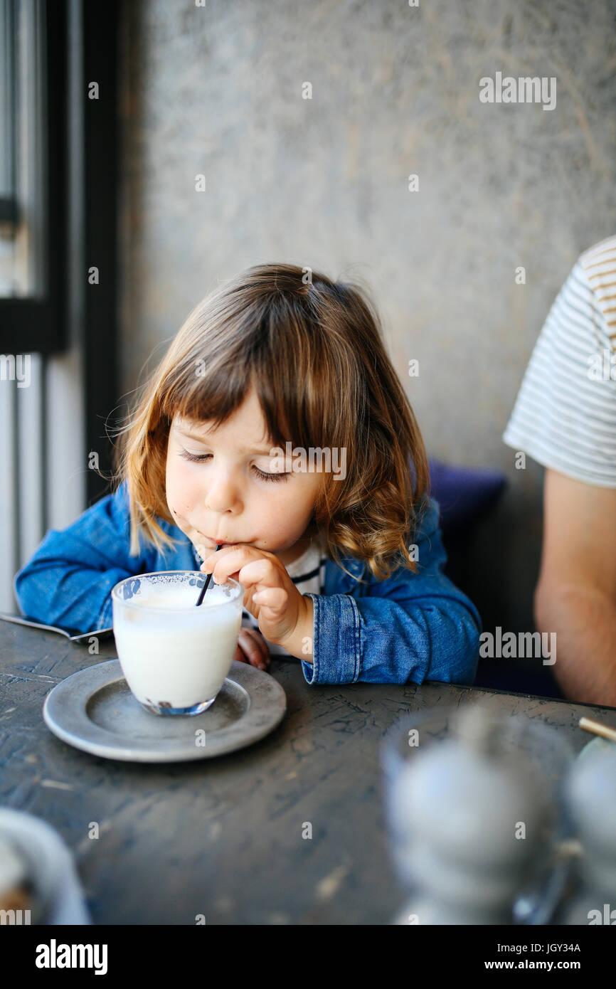 Mädchen trinken Milch im café Stockbild