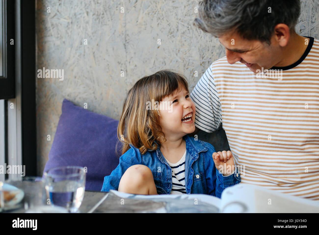 Mädchen lacht mit Vater im café Stockbild