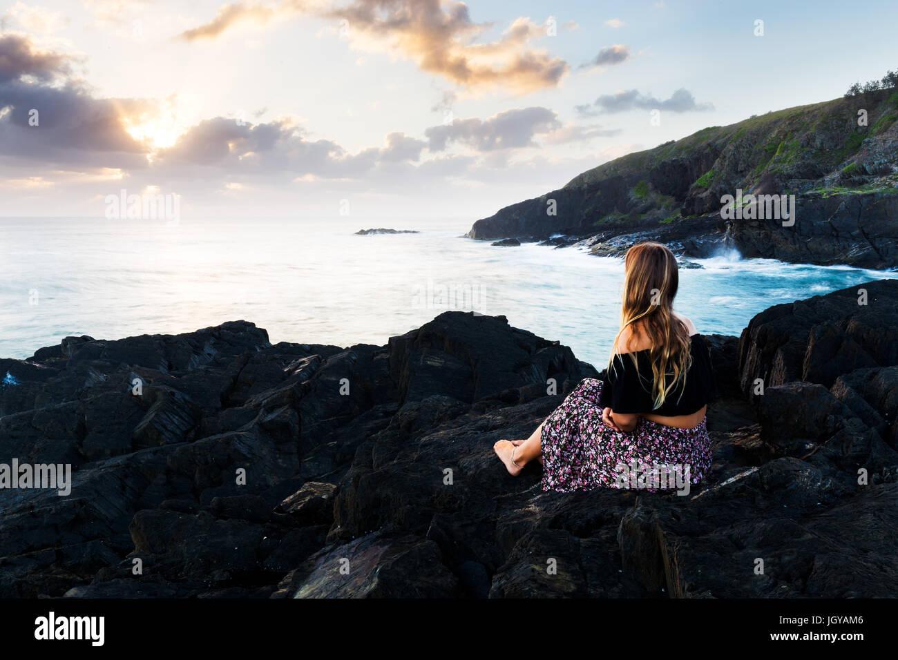Ein schönes Bohème-Stil Mädchen sitzt auf einer felsigen Landzunge und Uhren die Morgensonne über Stockbild