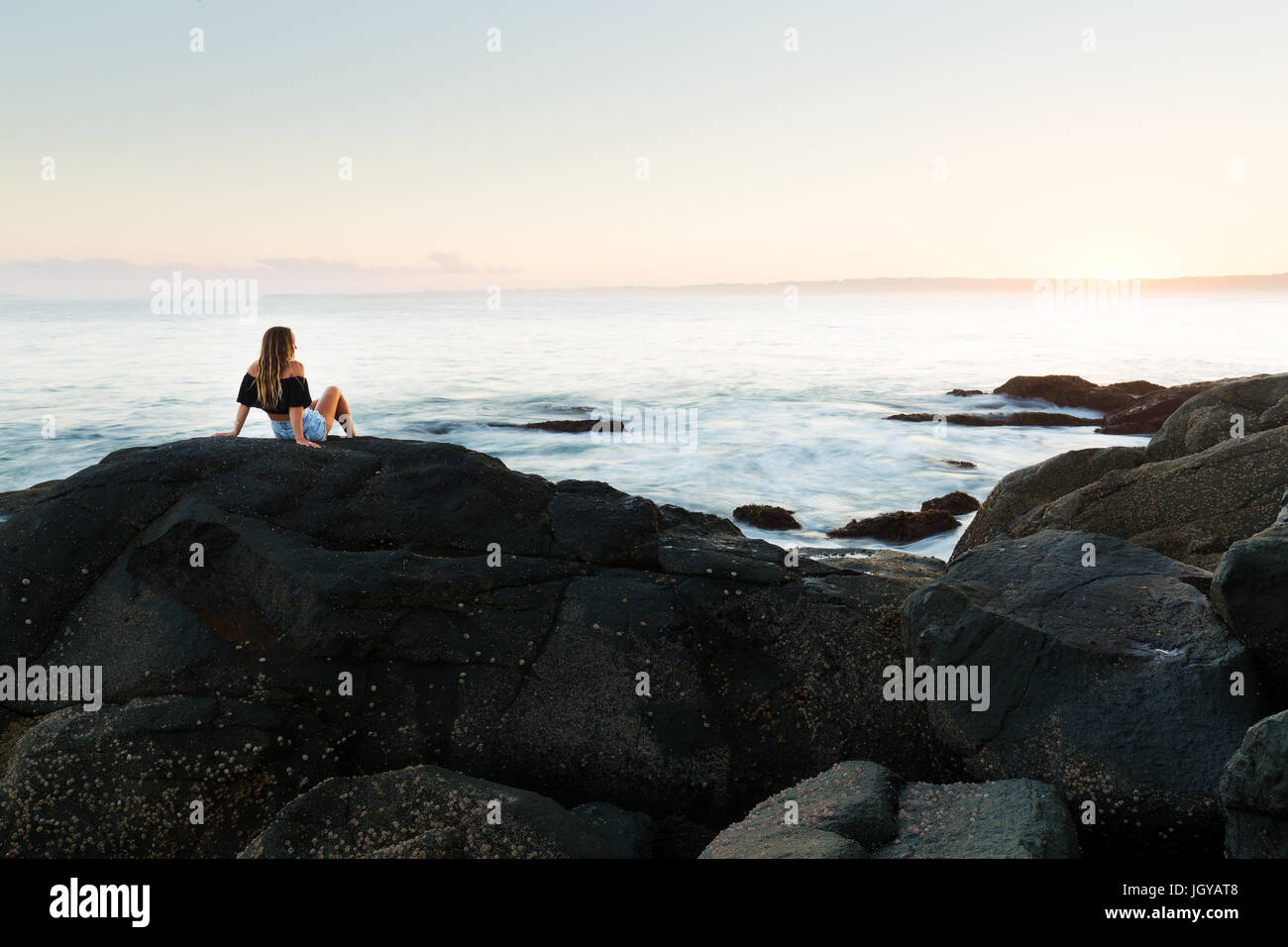 Ein gesundes junges Mädchen sitzt auf einem Stein und beobachtet den Sonnenuntergang über einem herrlichen Stockbild