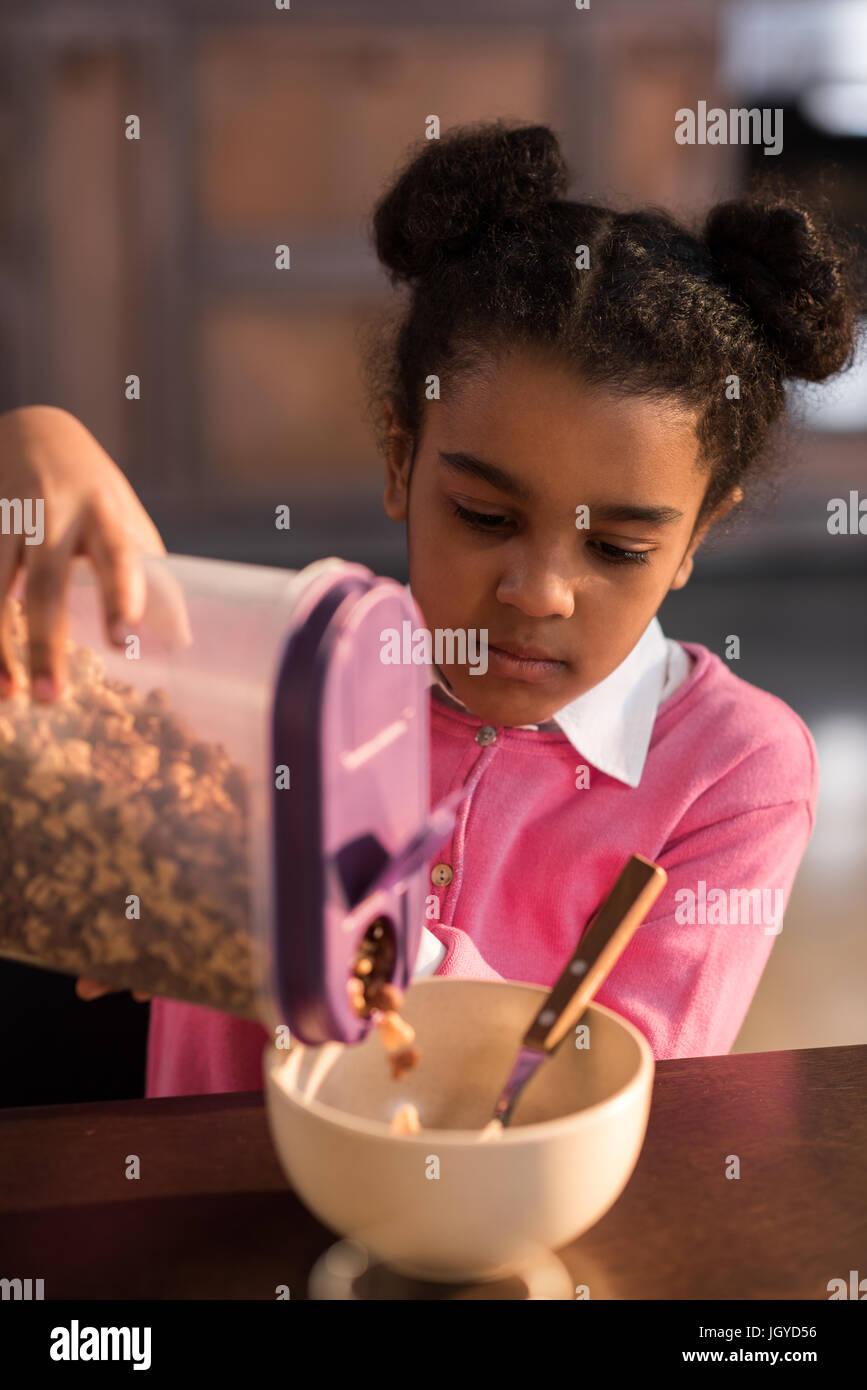 Porträt von fokussierten Mädchen Füllung Schüssel mit Flocken zum Frühstück Stockbild