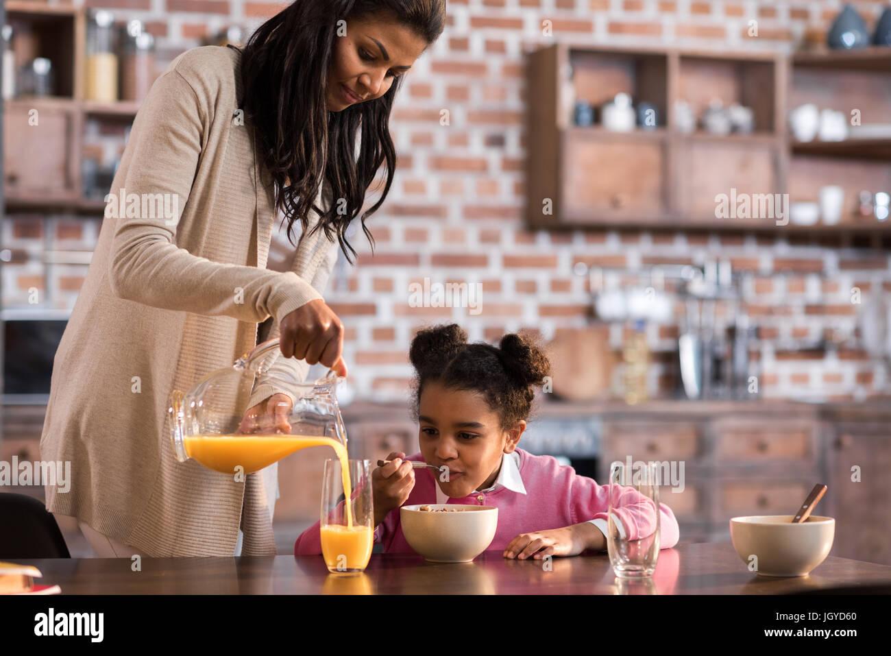 Mutter Tochter Glas Saft überfluten, während des Frühstücks zu Hause Stockbild
