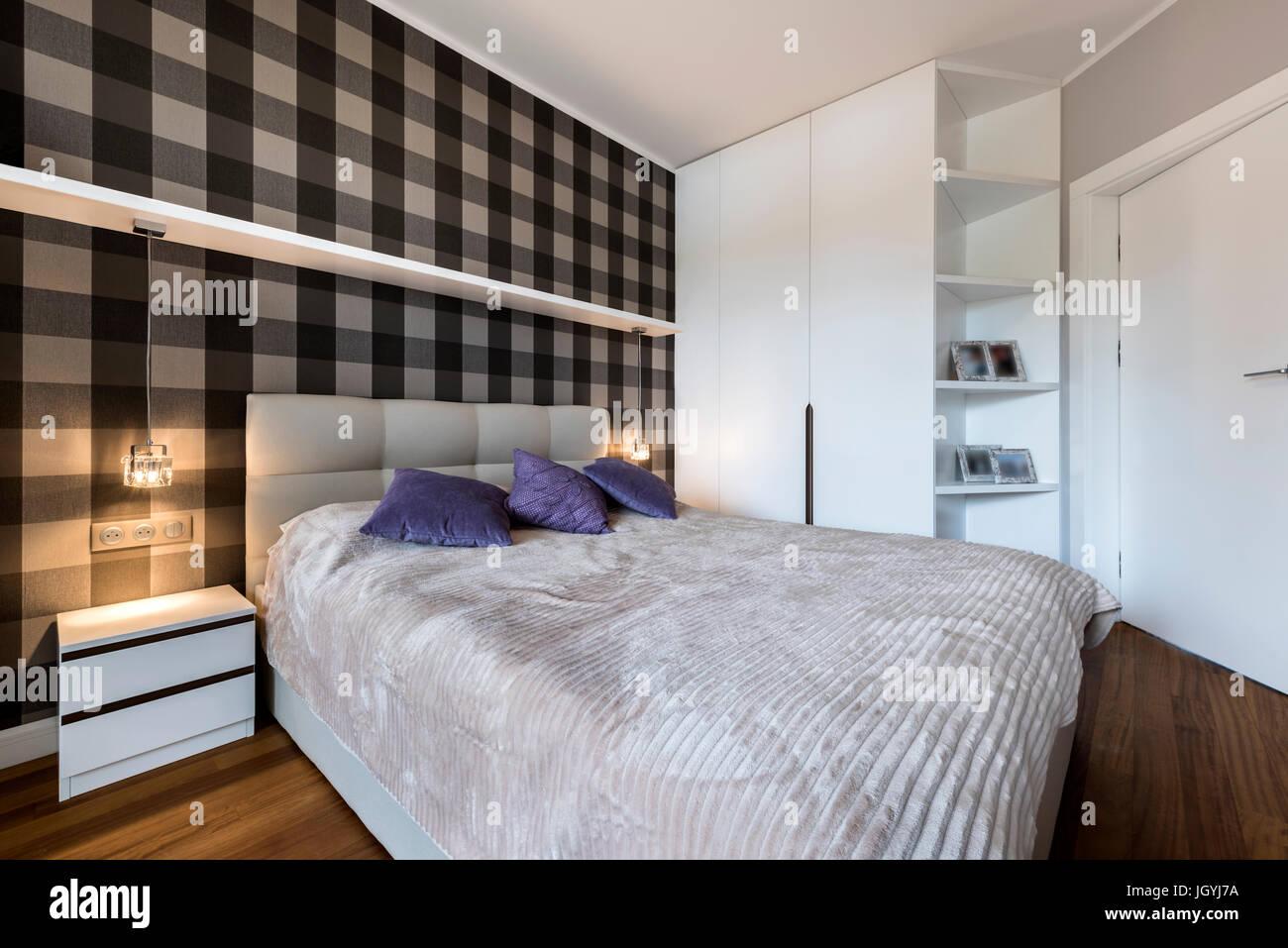Moderne Schlafzimmer mit Schachbrettmuster an der Wand und Schrank ...
