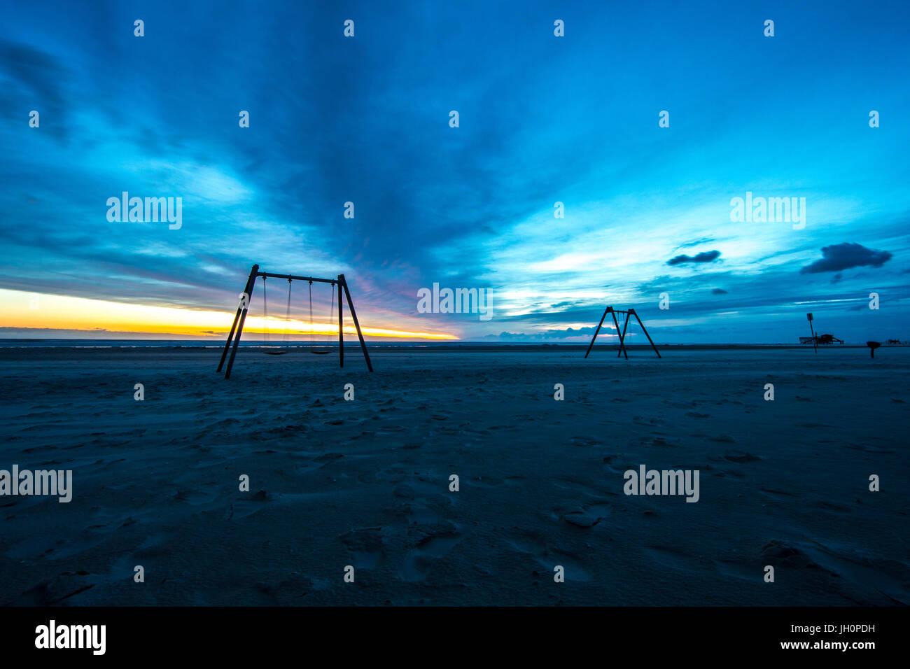 Dämmerung auf dem Strand von Sank Peter Ording in Norddeutschland. Schaukeln sind sanft bewegen während Stockbild