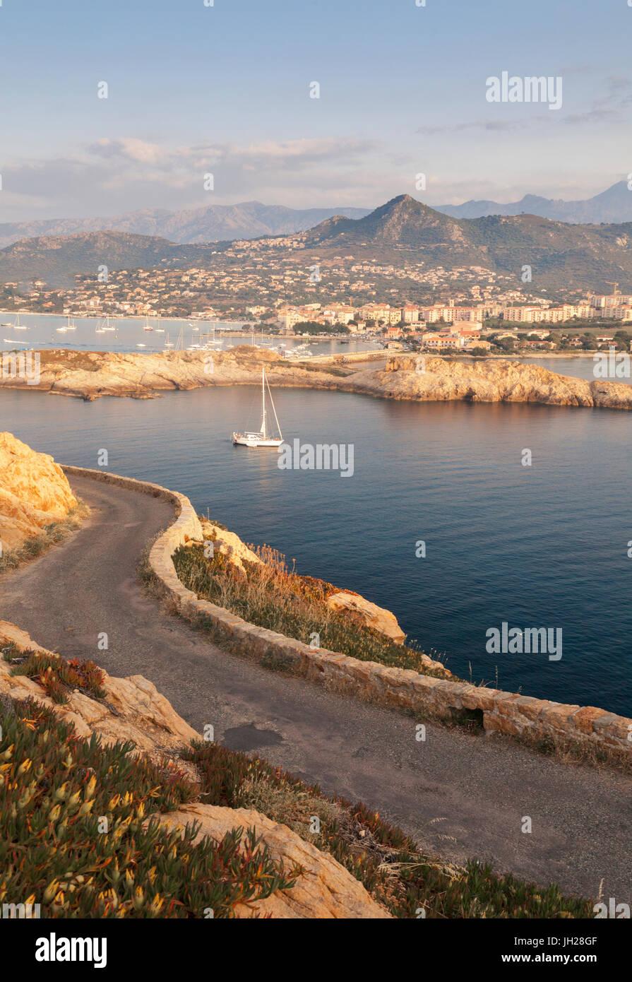 Ein Segelboot im kristallklaren Meer rund um das Dorf von Ile Rousse bei Sonnenuntergang, Balagne Region, Korsika, Stockbild