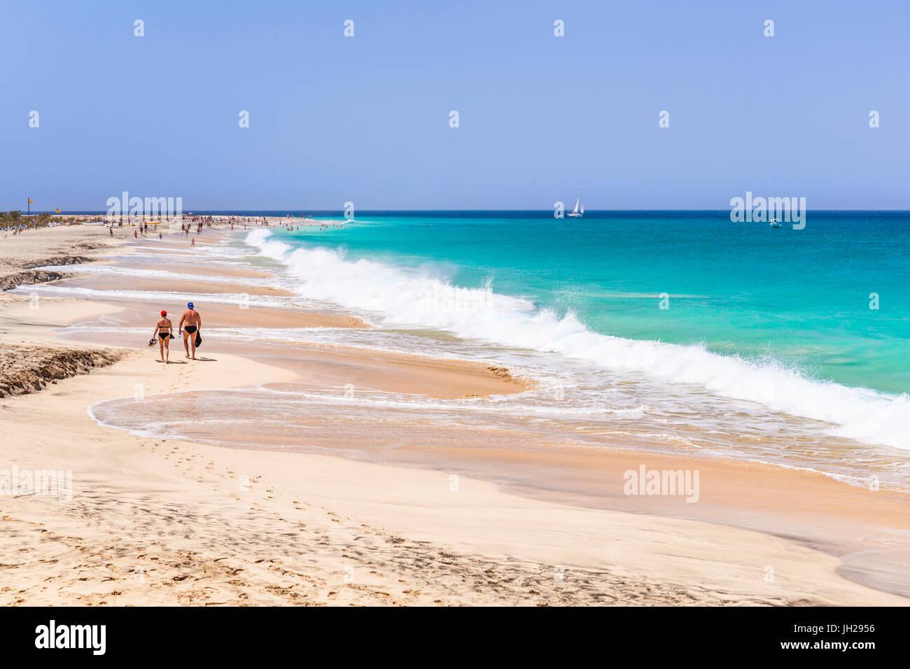 Touristen zu Fuß entlang des Sandstrandes, Ponta Preta beach, Santa Maria, Insel Sal, Kap Verde, Atlantik, Stockbild