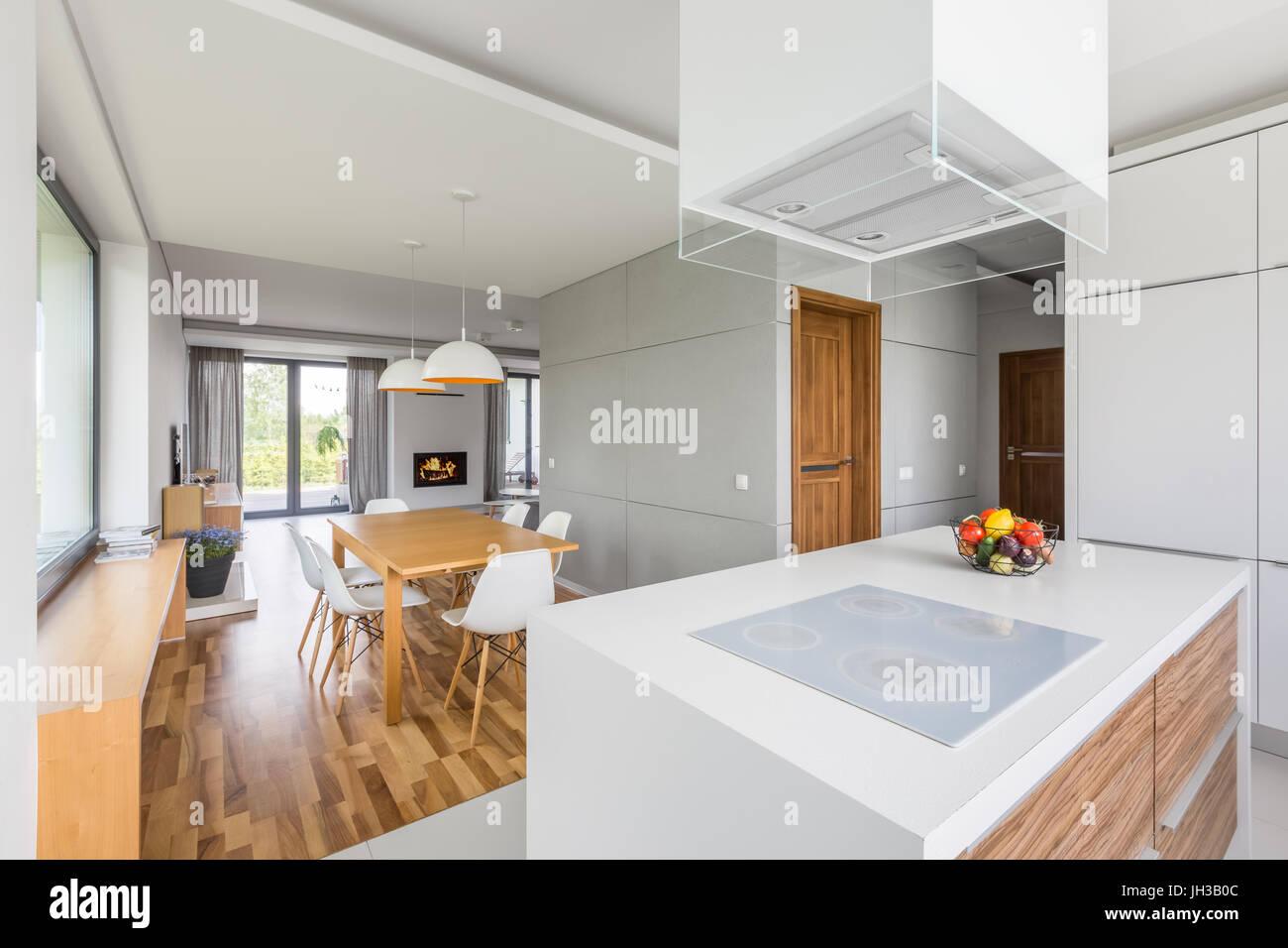 Küche mit Insel und Speisesaal mit Holztisch und weiße Stühle ...