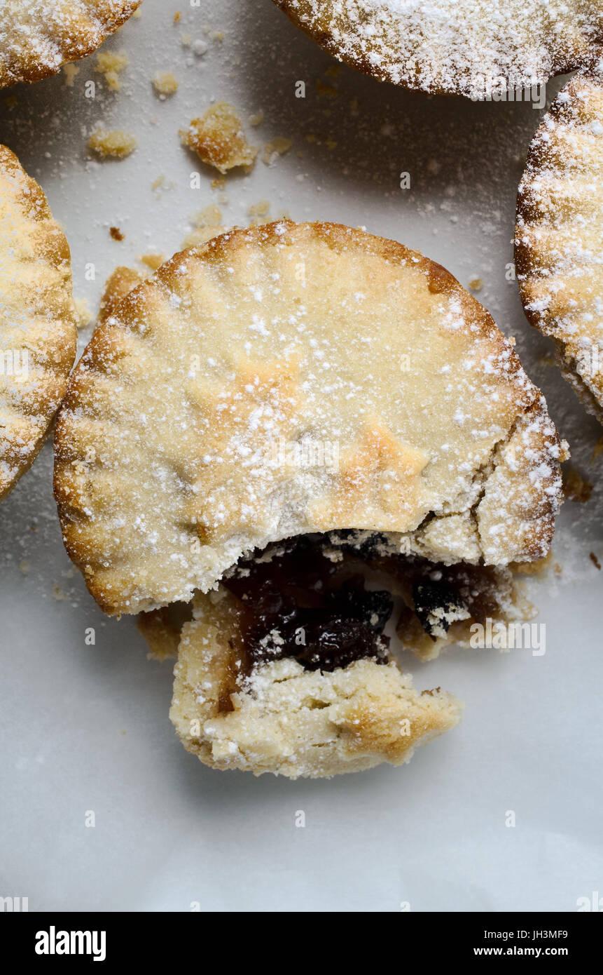 Overhead Nahaufnahme von einem Mince Pie in einer Gruppe, aufgebrochen als ob teilweise gegessen.  Weiße Glasur Stockbild