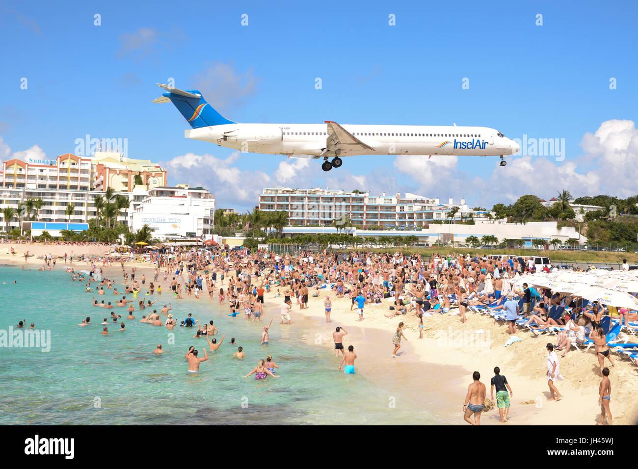 großes Flugzeug fliegt niedrig über Maho Beach in St. Maarten, Karibik, bekannt als Flugzeug-Strand Stockbild