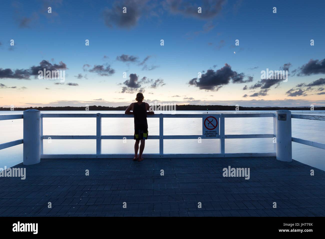 Eine Person sieht das Meer allein von einem Pier nach Einbruch der Dunkelheit in Australien. Stockfoto
