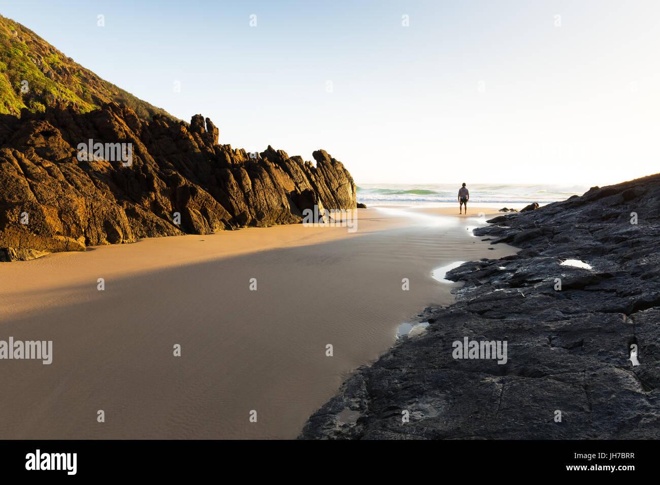 Eine Person steht allein an einem einsamen Strand in Australien und sieht die helle Morgensonne leuchten die Küste Stockbild