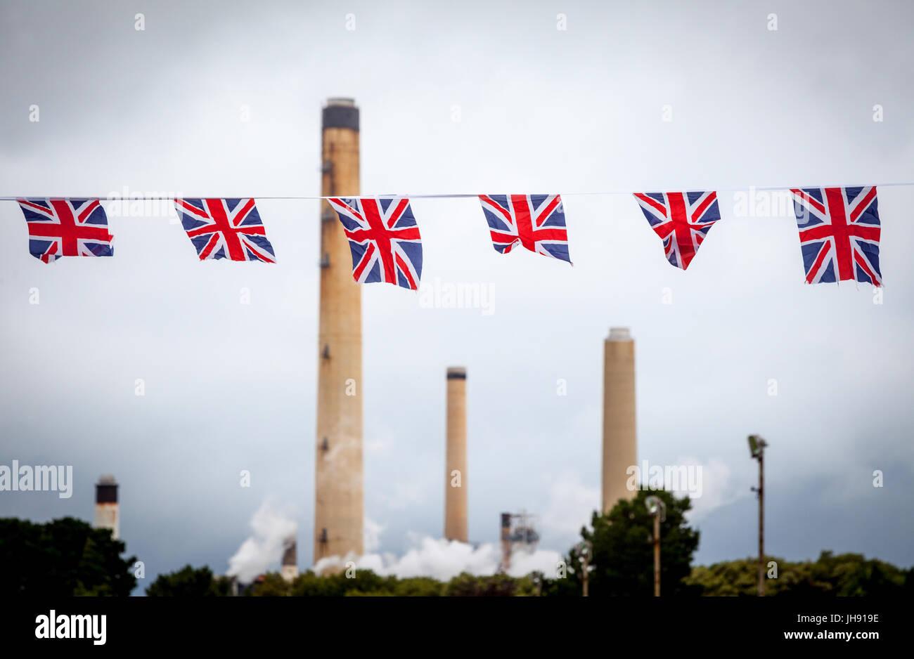 Raffinerie-Schornsteine mit Union Jack Bunting Flags im Vordergrund Stockbild