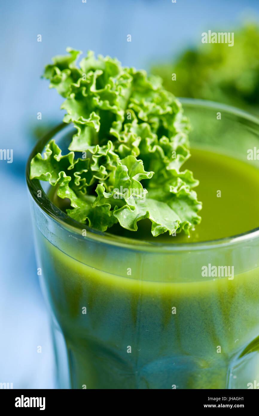 ein Smoothie Grünkohl serviert in einem Glas, gekrönt mit einem Blatt von Kale, auf einem blauen rustikalen Holztisch Stockfoto