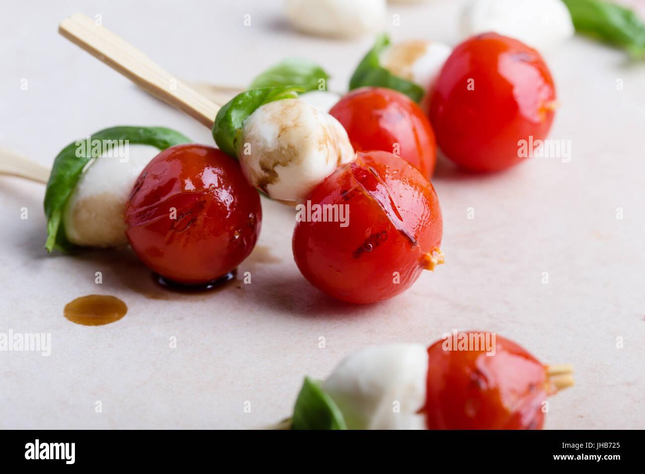 Gegrillte Caprese-Spieße auf grauem Hintergrund, traditionelle italienische Küche Stockbild