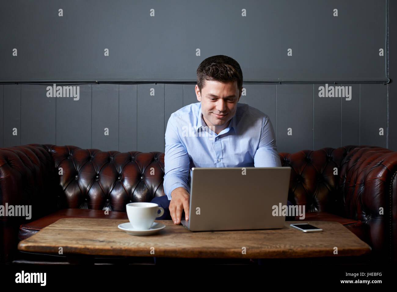 Mann arbeitet am Laptop im Internet-Cafe Stockbild