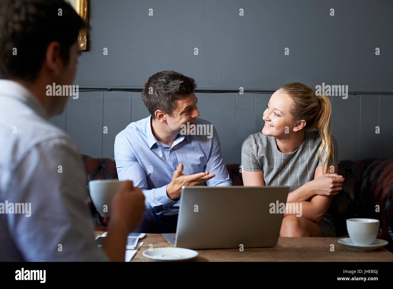 Drei Geschäftsleute treffen im Cafe Stockbild