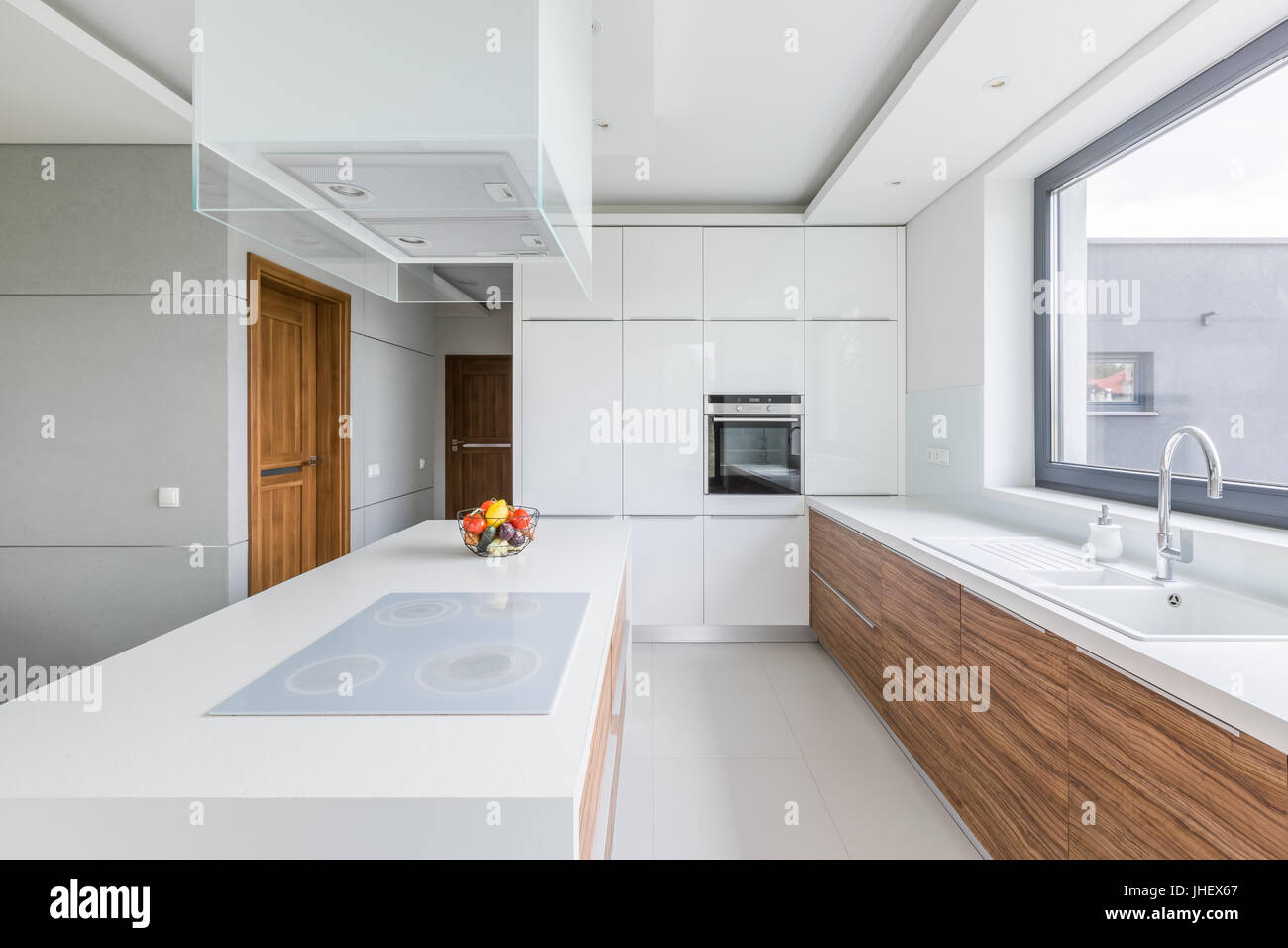 Weiße Küche mit Insel, lange Arbeitsplatte und hölzerne Schränke ...
